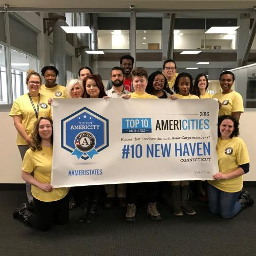 "Fifteen people in yellow AmeriCorps shirts hold a sign that reads ""Top 10 AmeriCities: #10 New Haven"""