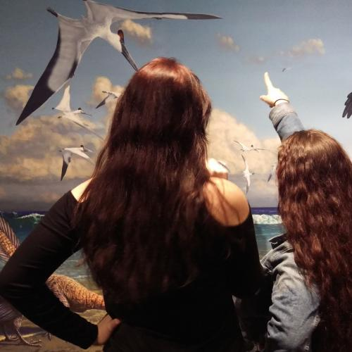 Two students examine a mural in the new Art of Archaeopteryx exhibit.
